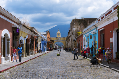 Antigua, Guatemala - April 16, 2014: View of a cobblestone street in the old city of Antigua with the Agua Volcano on the background, in Guatemala Editorial