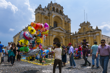 Antigua, Guatemala - April 17, 2014: Young boy selling baloons in a street of the old city of Antigua with the San Pedro Hospital on the background, in Guatemala Editorial