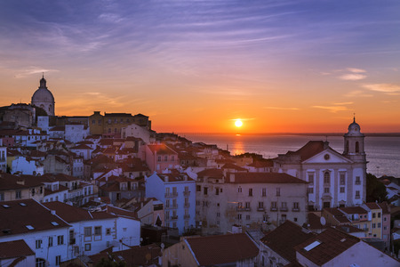 View of the Alfama neighborhood from the Portas do Sol viewpoint at sunrise in Lisbon, Portugal; Concept for travel in Portugal Stock Photo