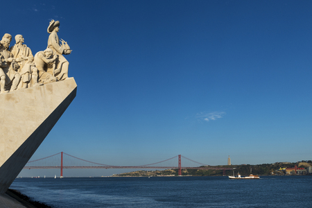 Detail of the Monument of the Discoveries (Padrao dos Descobrimentos) in the Tagus River in Lisbon, Portugal, with the 25 of April bridge (Ponte 25 de Abril) on the background; Concept for travel in Portugal and travel in Lisbon