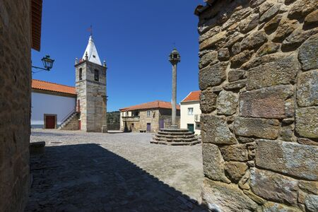 windows: View of the central square of the historic village of Castelo Mendo, in Portugal, with a church and pillory; Concept for travel in Portugal