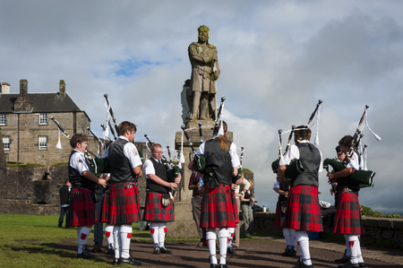 Stirling, Scotland - August 17, 2010: Band of pipers playing in front of the statue of Robert the Bruce in the Stirling Castle in Stirling, Scotland, United Kingdom Editorial