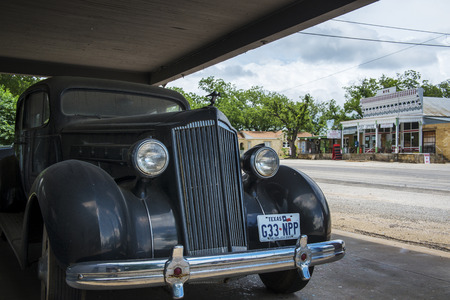 Hye, Texas - June 8, 2014: An old car with the general store and post office on the background in the small town of Hye in Texas, USA.