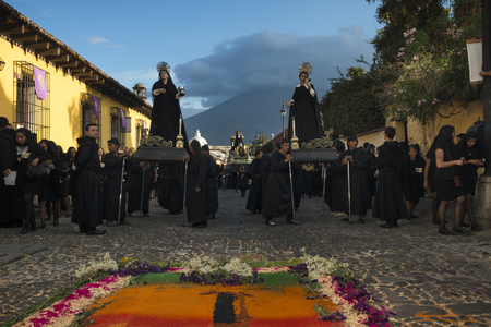 Antigua, Guatemala - April 19, 2014: People wearing black robes in a street of the old city of Antigua during a procession of the Holy Week in Antigua, Guatemala