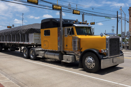 Yellow truck in a highway crossing a small american town; Concept for transportation and transportation background