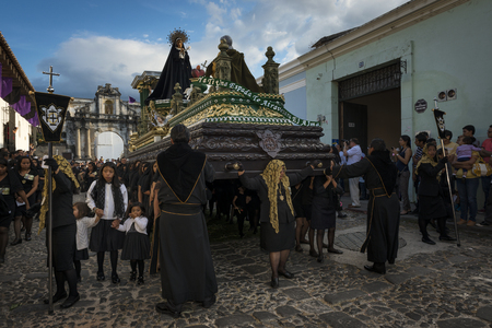 Antigua, Guatemala - April 19, 2014: Women dressed in black carrying a giant float in a street of the old city of Antigua during a procession of the Holy Week, in Antigua, Guatemala Editorial