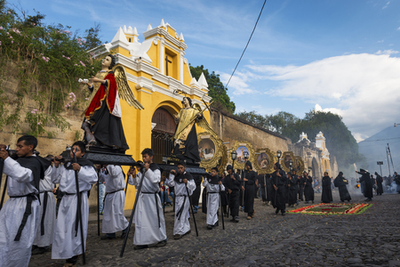 Antigua, Guatemala - April 19, 2014: Men carrying parade floats in a street of the old city of Antigua during a procession of the Holy Week, in Antigua, Guatemala