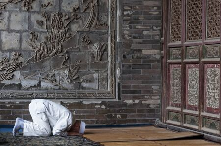 Xi'An, China - August 5, 2012, 2017: One man praying at the Xi'An Great Mosque in the city of Xi'An in China, Asia. 에디토리얼