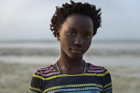 Orango Island, Guinea-Bissau - February 2, 2018:  Portrait of a beautiful young girl at the beach in the island of Orango at sunset.