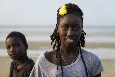 Orango Island, Guinea-Bissau - February 2, 2018:  Portrait of a beautiful young girlr and a boy in the beach at the island of Orango. 에디토리얼