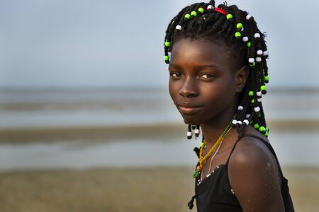 Orango Island, Guinea-Bissau - February 2, 2018:  Portrait of a beautiful young girl at the beach in the island of Orango at sunset.