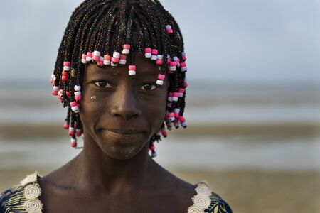 Orango Island, Guinea-Bissau - February 2, 2018:  Portrait of a beautiful young girl in the beach in the island of Orango at sunset. 에디토리얼