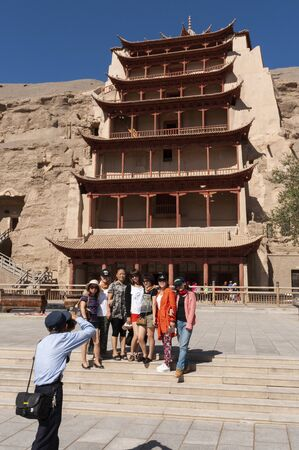 Dunhuang, China - August 8, 2012: Tourists at the entrance of the Mogao Caves near the city of Dunhuang, in the Gansu Province, China. 에디토리얼