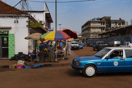 Bissau, Republic of Guinea-Bissau - February 5, 2018: Street scene in the city of Bissau with an old taxi and vendors, in Guinea-Bissau, West Africa