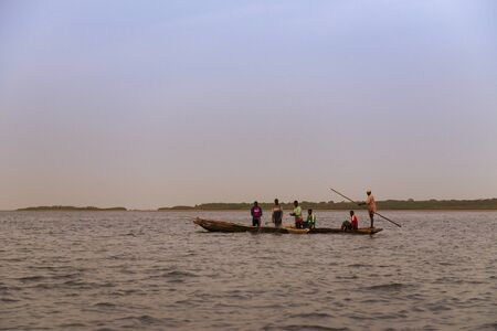 Orango Island, Guinea-Bissau - February 3, 2018:  Fishermen collecting the nets in an old traditional fishing canoe near the island of Orango. Redakční
