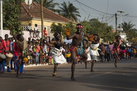 Bissau, Republic of Guinea-Bissau - February 12, 2018: Group performance during the Carnival Celebrations with men and women wearing traditional costumes in the city of Bisssau.