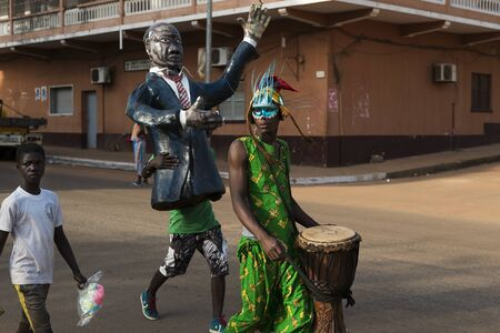 Bissau, Republic of Guinea-Bissau - February 12, 2018: People wearing costumes during the Carnival celebrations in a street of the city of Bisssau.