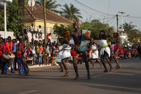 Bissau, Republic of Guinea-Bissau - February 12, 2018: Men and women wearing traditional clothing at a parade during the Carnival Celebrations in the city of Bisssau. 에디토리얼