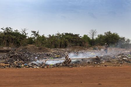 Bissau, Republic of Guinea-Bissau - February 5, 2018: Man walking in a landfill in the outskirts of the city of Bissau, in Guinea-Bissau, West Africa