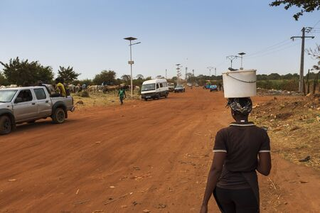 Bissau, Republic of Guinea-Bissau - February 5, 2018: Woman carrying a bucket on her head and walking along a dirt road on the outskirts of the city of Bissau, in Guinea-Bissau, West Africa