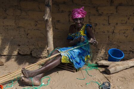 Orango Island, Guinea-Bissau - February 3, 2018: An old woman working in front of her hut at the village of Eticoga in the island of Orango. 에디토리얼