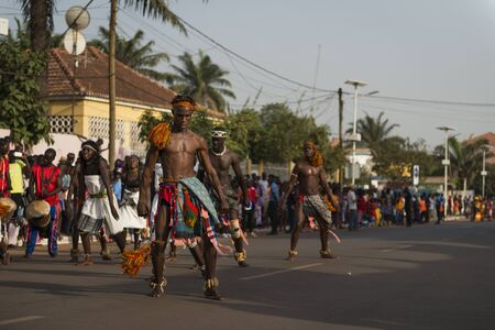 Bissau, Republic of Guinea-Bissau - February 12, 2018: Group of men and women wearing traditional clothing performing during the Carnival Celebrations in the city of Bisssau.