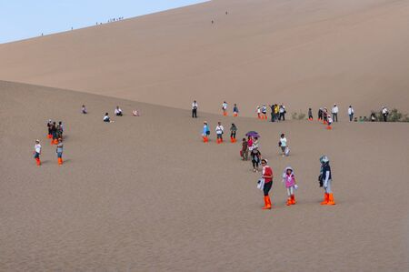 Dunhuang, China - August 8, 2012: Group of Chinese tourists at the Crescent Moon Lake near the city of Dunhuang, in the Gansu Province, China.
