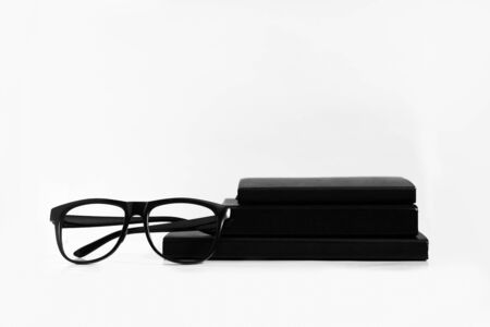 Black and white still life: opened blank notepad with linear pages, notebooks, pen, glasses, watch, cup of coffee and lipstick. Business accessories. Top view, flat lay.