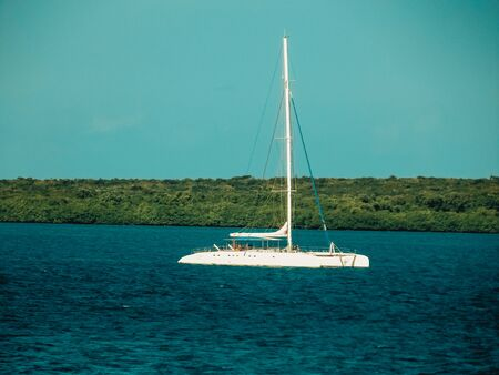 Motorsailer at anchor on steep green coast hill background. Luxury pleasure craft yacht with lowered sails on calm sea water. Travel on Varadero, Cuba, Carribean beach, blue ocean and cloudy sky.