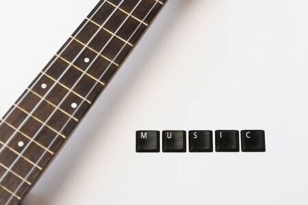 ukulele on isolated background with lettering music on white isolated background, top view, fretboard with copy space Stock Photo