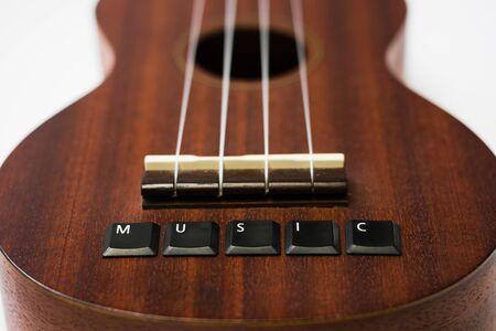ukulele on isolated background with lettering music on white isolated background, bottom view