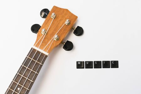ukulele on isolated background with lettering music on white isolated background, top view of fretboard with copy space Stock Photo
