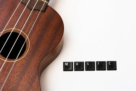 ukulele on isolated background with lettering music on white isolated background, front view with copy space