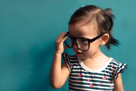 Beautiful serious children (kid, girl) holding glasses, blue isolated background with copy space.