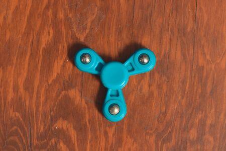 fidget spinner on wooden desk in isolated background