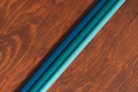 three colored pencils on wooden desk in isolated background, diagonal view Stock Photo