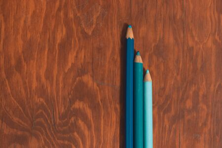 three colored pencils on wooden desk in isolated background to fill with copy space