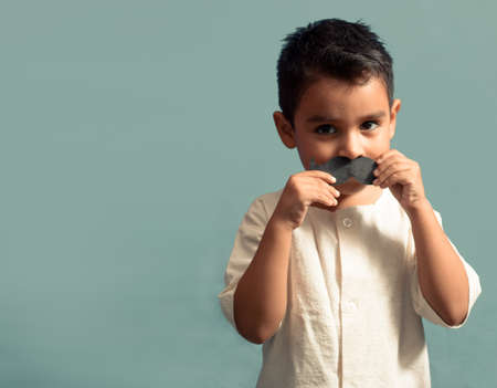 little kid joking with a fake paper moustache. Happy child playing in home. Isolated background.