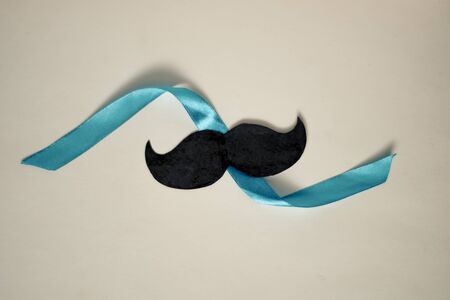 Moustache on isolated background, blue ribbon, fathers day concept, with copy space
