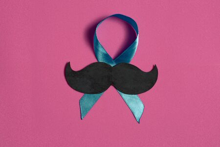 Moustache and blue ribbon on pink isolated background, international cancer prostate day concept, with copy space
