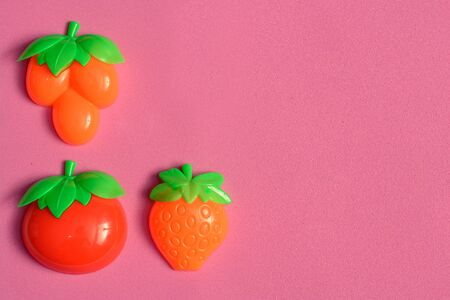 Plastic fruits and vegetables collection set isolated on pink background