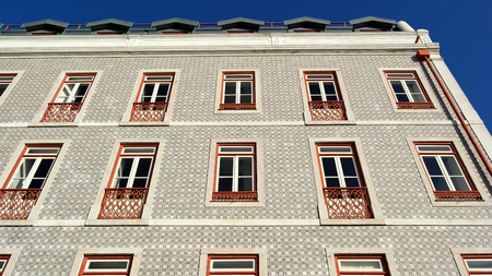 Detail of an old building with portuguese tiles and red and white windows, Lisbon, Portugal