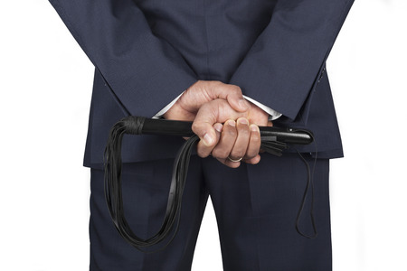 Leather whip held by dominant master in a suit