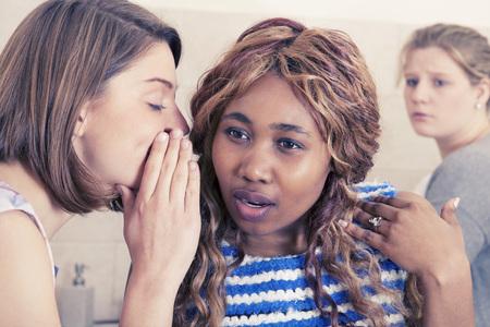 gossiping: Two young girls gossiping