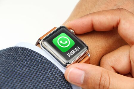 Business man checking messages with a smart watchs app