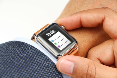 suited up: Business man making a To do list with a smart watchs app Stock Photo