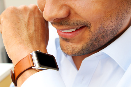 suited up: Business man talking to his smart watch