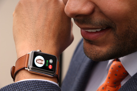 suited up: Businessman taking a call on his smart watch Stock Photo