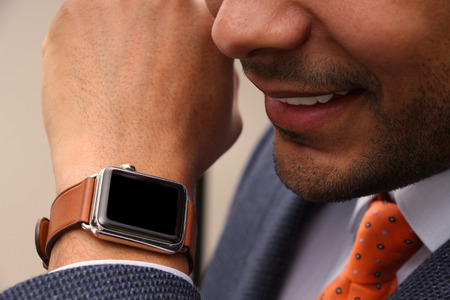 suited up: Businessman talking to his SmartWatch