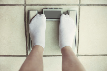 part of me: Womans feet on bathroom scale. Diet concept